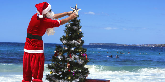Man dressed as Santa Claus decorating christmas tree on beach, rear view